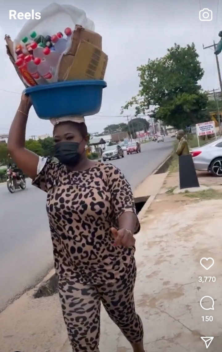 Sista Afia carryng water on the street